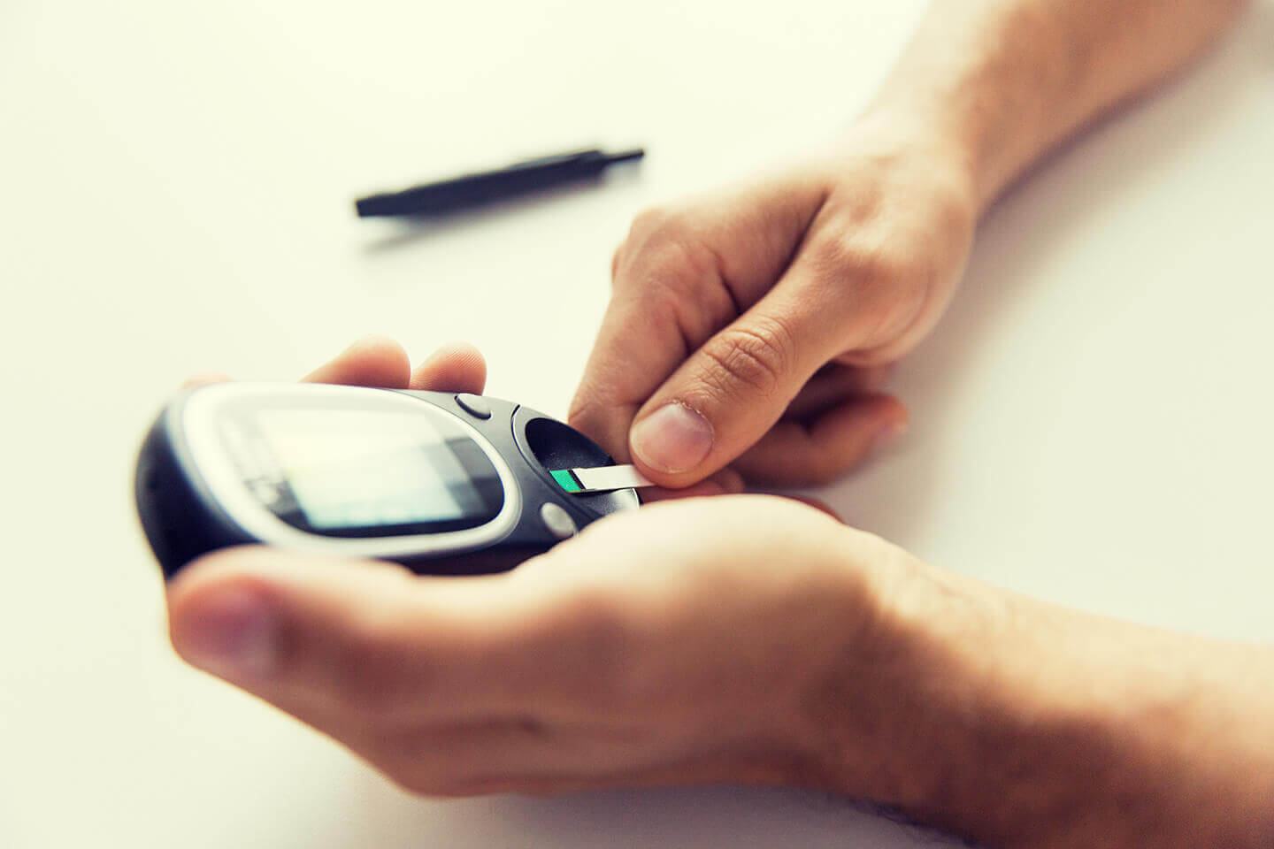 Person holding blood sugar monitoring device